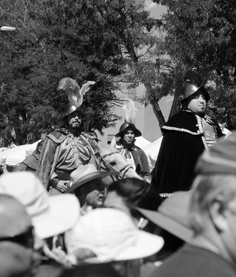 Dignitaries dressed as Spanish conquistadores attempt to ride through a crowd of protesters during the 2016 Entrada in front of the Palace of the Governors.